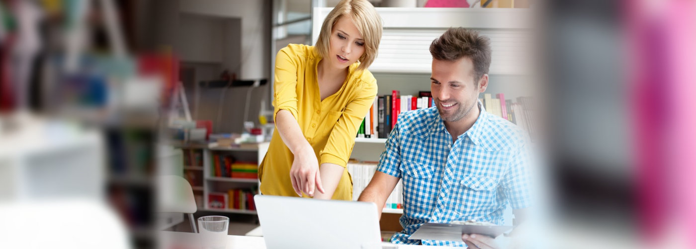 woman assisting man working  on a laptop